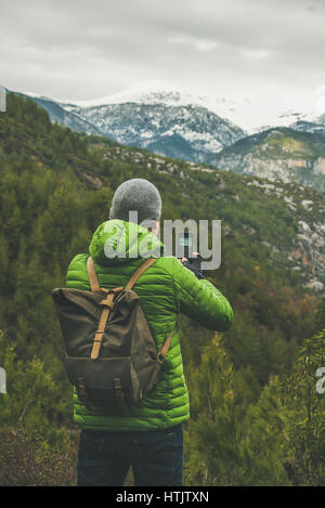 Young man traveller wearing bright clothes making photo of landscape - Stock Photo