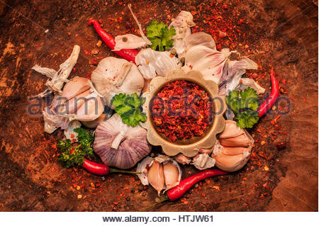 Organic garlics,  hot peppers with spices on wooden rustic table - Stock Photo