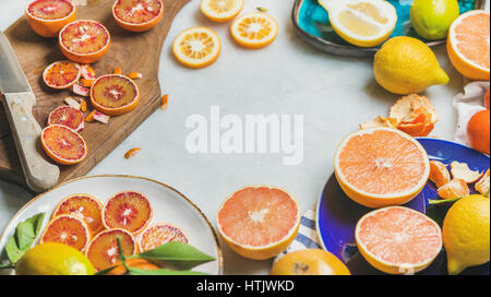 Natural fresh citrus fruits in ceramic plates and wooden board - Stock Photo