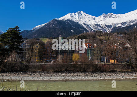 View across the River Inn in Innsbruck, Austria, showing mountains of the Austrian Alps and local buildings. - Stock Photo