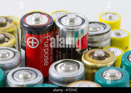 AA alkaline batteries with selective focus on two red black protruding batteries - Stock Photo