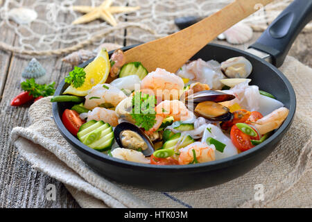 Fried mixed seafood and fresh colorful vegetables served in an iron frying pan with slices of baguette with herb - Stock Photo