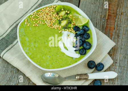 Green smoothie from kale and banana with kiwi in the bowl. Love for a healthy vegan food concept - Stock Photo