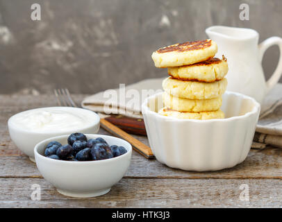 Cottage cheese pancakes for breakfast with blueberries and sour cream. - Stock Photo
