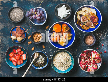 Fresh and dried fruit, chia seeds, oatmeal, nuts, honey - Stock Photo