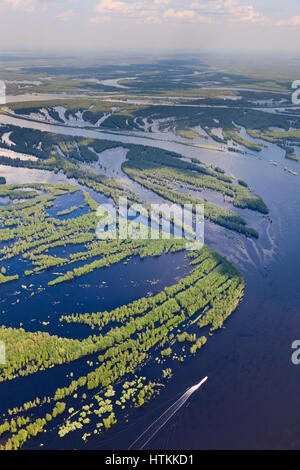 View from above of pleasure boat on forest river during flood - Stock Photo