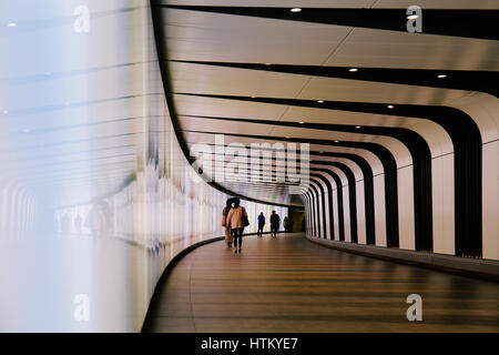 Commutes walking through futuristic looking pedestrian tunnel featuring an LED integrated light wall in Granary - Stock Photo