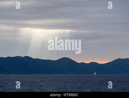 Sun rays shining through stormy dark clouds above a silhouette of hills and mountains mountain at sunset with yacht - Stock Photo