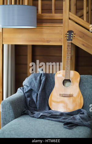 Cozy living room with guitar on the sofa in the wooden house - Stock Photo