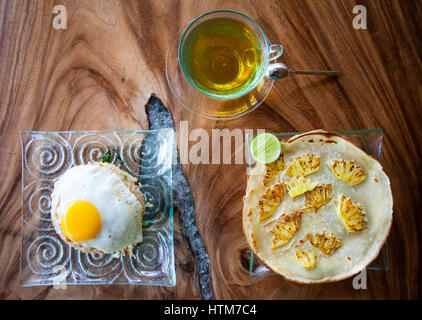 Traditional Asian Breakfast, rice with egg, pancake with pineapple and tea on textured wooden table - Stock Photo