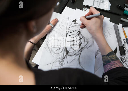 Girl tattoo artist draws a sketch. Close-up of hands - Stock Photo