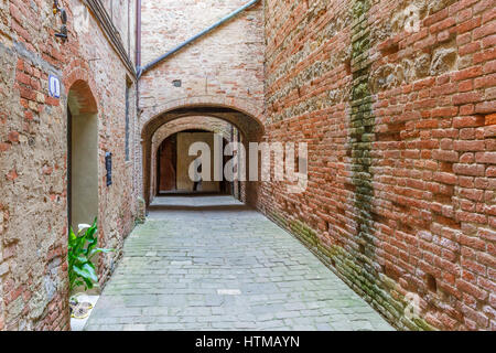 Alley with brick walls in an old Italian village - Stock Photo