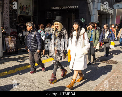 Two women in fashionable clothes walking in the Shibuya shopping district, Tokyo Japan. - Stock Photo