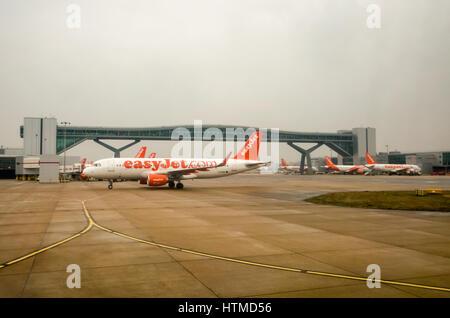 London Gatwick. England UK.  EasyJet aeroplanes on London Gatwick airport runway with a foot bridge that crosses - Stock Photo