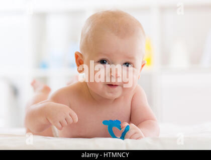 Portrait of adorable baby. Kid boy lying on his stomach and holding teether toy. - Stock Photo