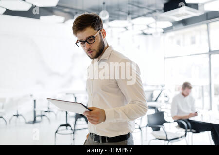 Confident businessman wearing shirt and glasses  using tablet - Stock Photo