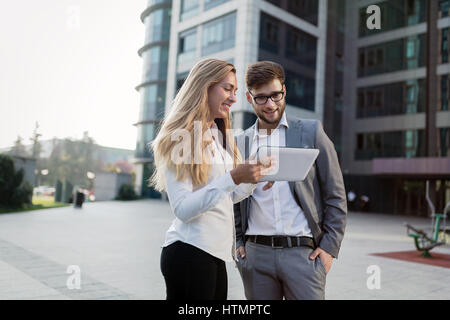 Business people walking outdoors and using phones tablets - Stock Photo