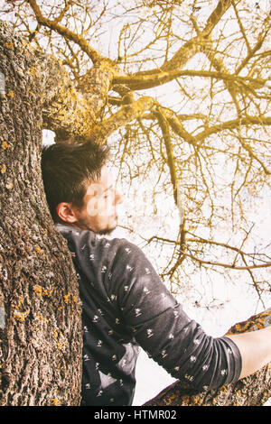 Young man lying on the top of a tree - Stock Photo