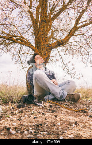 Young hipster man taking shots near a blossom tree in spring - Stock Photo