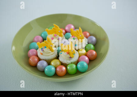 Close-up of colorful chocolate Easter eggs with cup cakes in bowl - Stock Photo