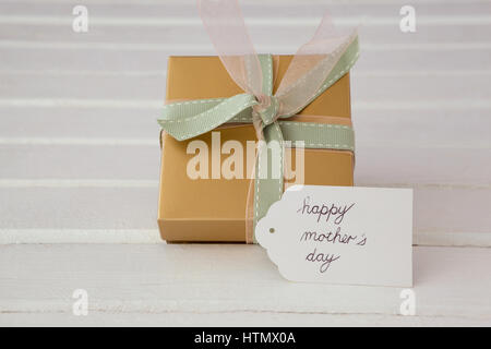 Happy mothers day card with gift box on wooden surface - Stock Photo
