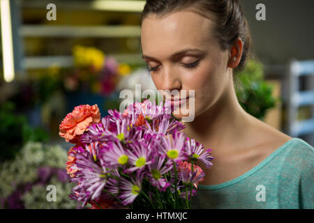 Woman smelling a bunch of flowers in flower shop - Stock Photo