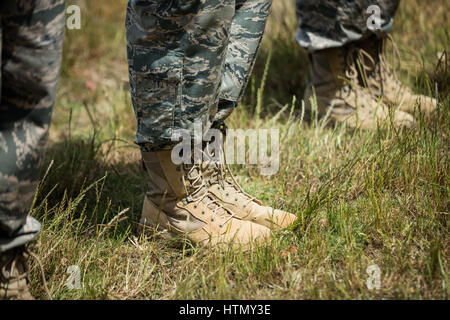 Low-section of military soldiers standing in line at boot camp - Stock Photo