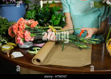 Female florist trimming flower stem at flower shop - Stock Photo