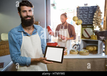 Portrait of smiling staff showing digital tablet at counter in market - Stock Photo