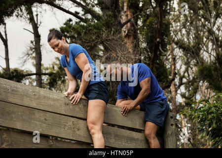Male trainer assisting woman to climb a wooden wall during obstacle course - Stock Photo