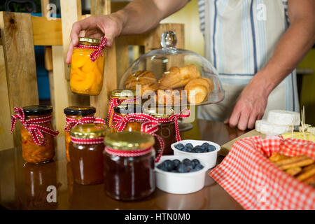 Shop assistant arranging jam and pickle jars in grocery shop - Stock Photo