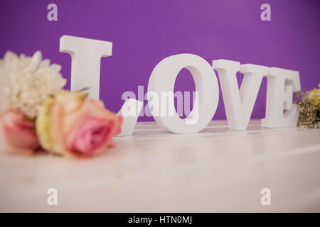 Flowers with alphabets forming love on white table - Stock Photo