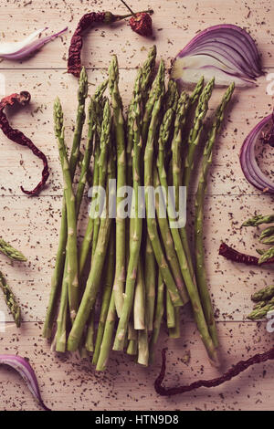 high-angle shot of a bunch of wild asparagus on a rustic wooden surface - Stock Photo