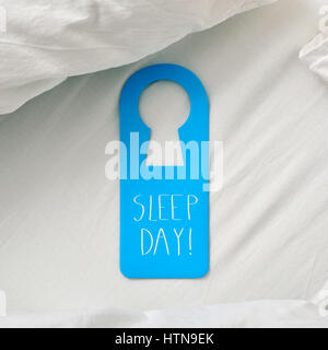 closeup of a blue door hanger with the text sleep day written in it, placed on a comfortable bed - Stock Photo