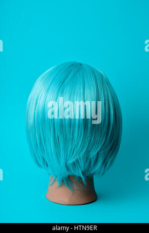 closeup of a blue wig in a mannequin head on a blue background - Stock Photo