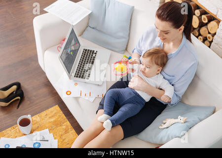 Wanna have some fun. Loving gentle classy mom playing with her child while taking some time off after comparing - Stock Photo