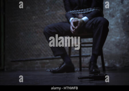 How can I get near it. Classy typical rich businessman being tied up and sitting on a chair while hoping getting - Stock Photo