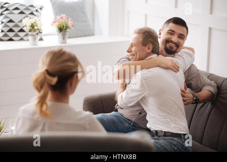 Loving couple. Joyful happy positive gay couple embracing each other and laughing while being in love - Stock Photo