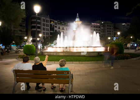 Three older people sit on a bench back to camera looking at the illuminated fountain in the Plaza del Campilo on - Stock Photo