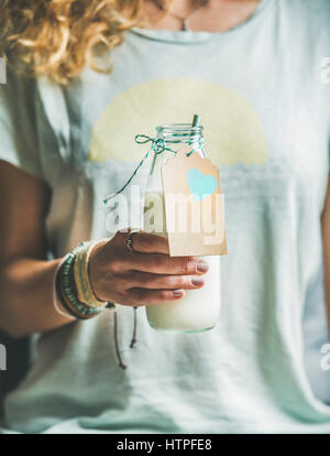 Young blond woman in grey light holding bottle of dairy-free almond milk in her hand. Clean eating, vegan, vegetarian, - Stock Photo