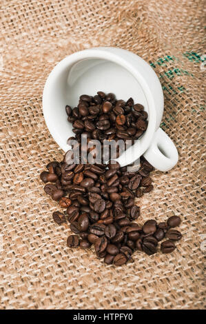 Coffee cup and beans on jute background - Stock Photo