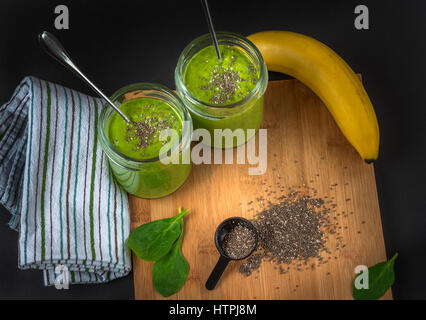 Green spinach, chia seed, banana and protein powder smoothie in two jars on the bamboo wooden surface, cloth napkin, - Stock Photo