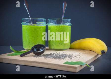 Green spinach, chia seed, banana and protein powder smoothie in two jars on the bamboo wooden surface and dark background. - Stock Photo