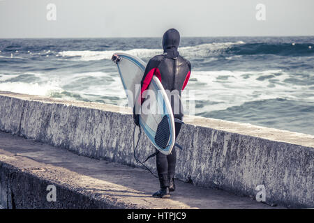 Surfer walks  into water wearing a wetsuit in winter. Cold surfing. Wave splash. waterproof suit. He has action - Stock Photo