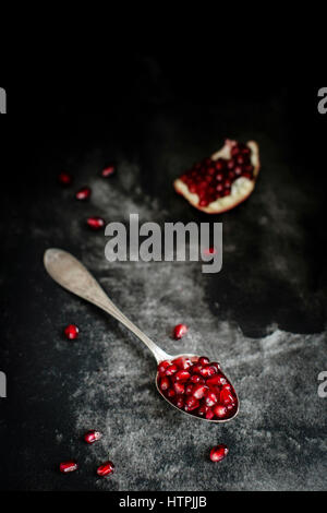 Fresh and juicy pomegranate seends on a dark background - Stock Photo