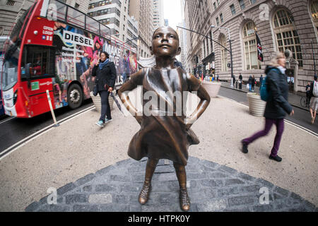 The bronze statue, 'The Fearless Girl' by the artist Kristen Visbal attracted attention at Bowling Green Park in - Stock Photo