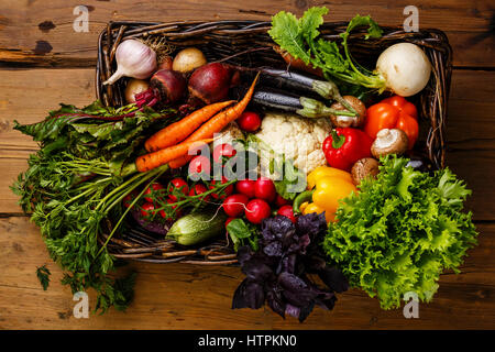 Fresh vegetables in basket on wooden background - Stock Photo