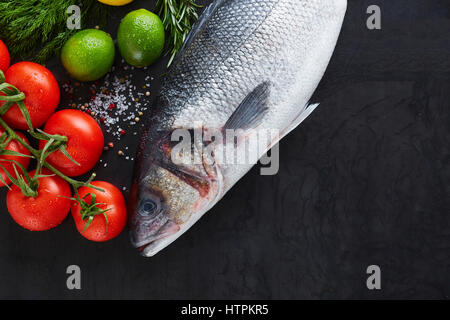 black rustic tabletop with raw products, fish, tomatoes, limes and lemons, top view