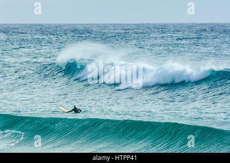 A surfer waits for the perfect wave, Dalmeny, South Coast, New South Wales, NSW, Australia - Stock Photo