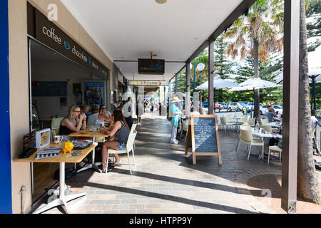 People Sat Outside A Small Cafe Or Restaurant In The Small